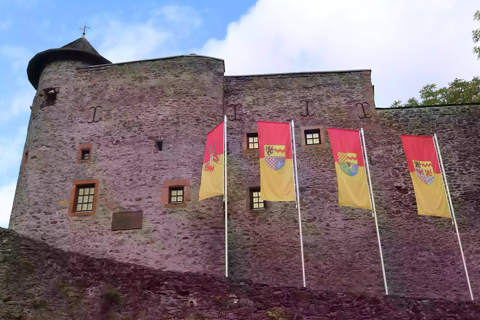 Red and yellow flags in front of the lower castle of Manderscheid, Eifel