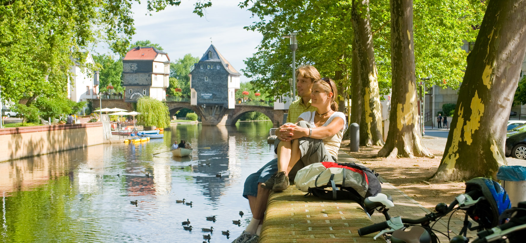 Relaxed couple in front of the bridge houses of Bad Kreuznach at Nahe river, Nahe