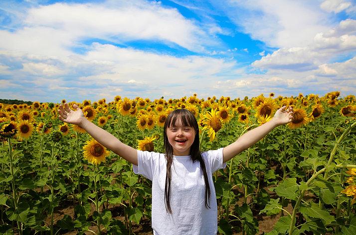 Lachendes Mädchen vor Sonnenblumenfeld