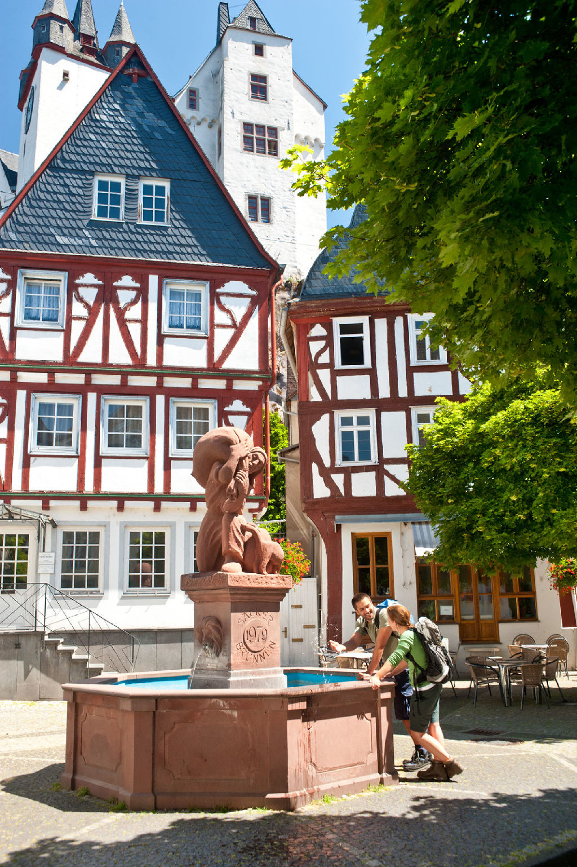 Hiker at the Säcker fountain in front of half-timbered houses in Diez, Lahntal